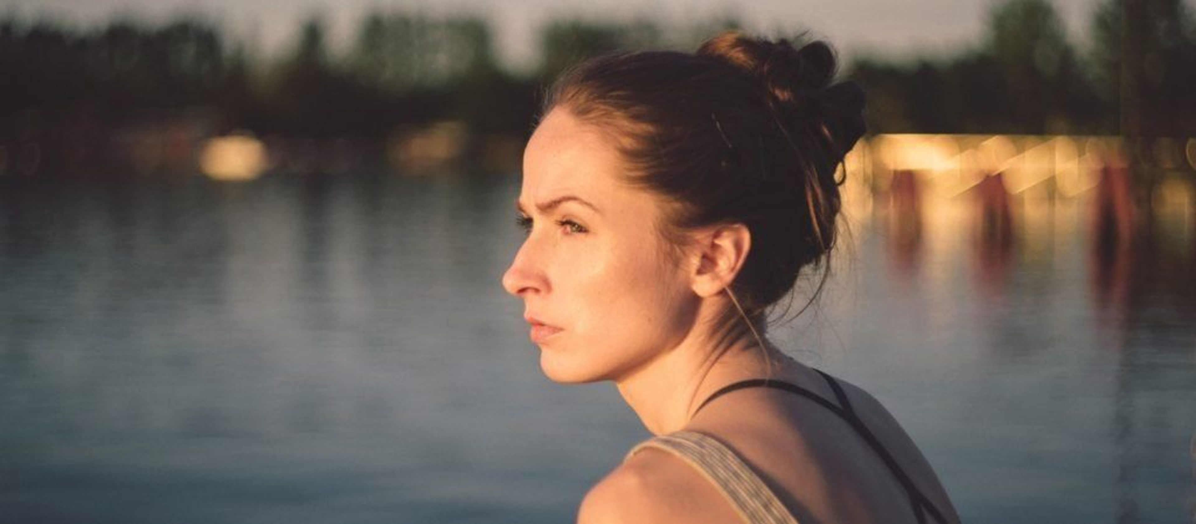 Woman sitting on dock on the water